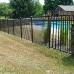 A simple 4' high Ornamental Aluminum pool enclosure. The fence is a nice compliment to the stone wall sculpture in the area.