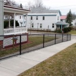 MAPLE STREET, ONEONTA  In 2009, we installed this 3 ½' high black vinyl chain link fence on Maple Street for the City of Oneonta. After a new sidewalk was installed, we core-drilled into the concrete to install this safety fence along the edge of a steep drop off.