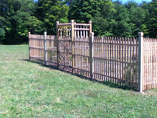COOPERSTOWN 2011  We built this 6' Economy Cedar fence around a vegetable garden to keep the deer out. The custom arbor was designed to support new grape vines.